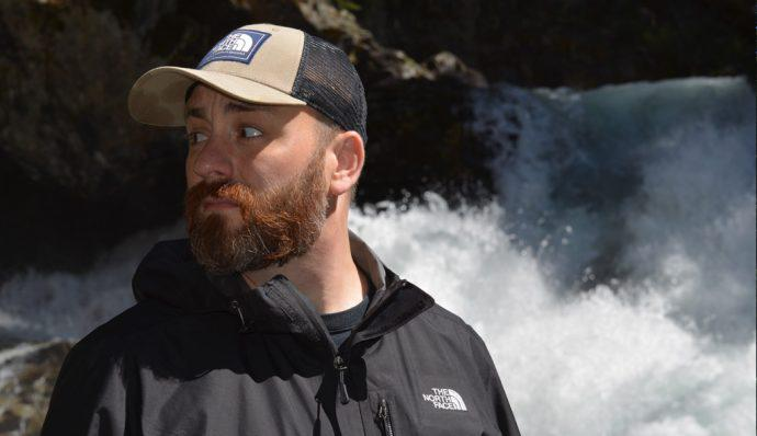 Author Jon Lewis standing in front of a waterfall