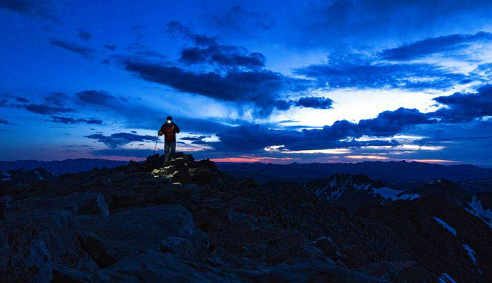 Hiker walks in the mountains at night