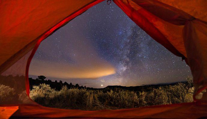 The view of the night's sky from within a red tent