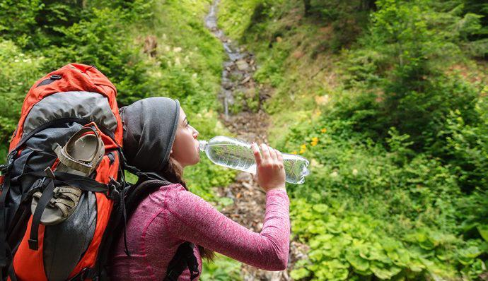 A day hiker stops on a hiking trail to take a drink from her water bottle.