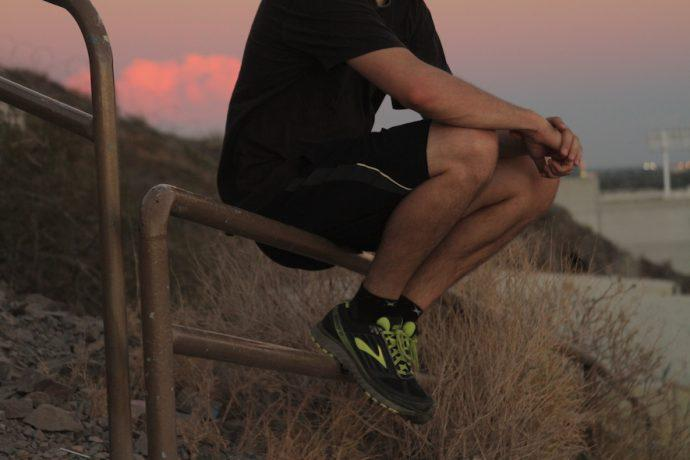 Man sits on fence while wearing Brooks Ghost 9 GTX® Shoes