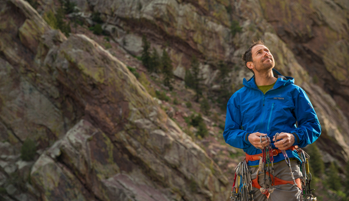 Man in blue jacket stands holding carabiners
